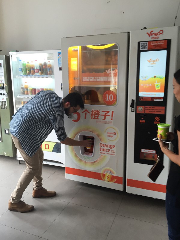 Alex getting fresh squeezed orange juice from a vending machine, paid for with his phone.
