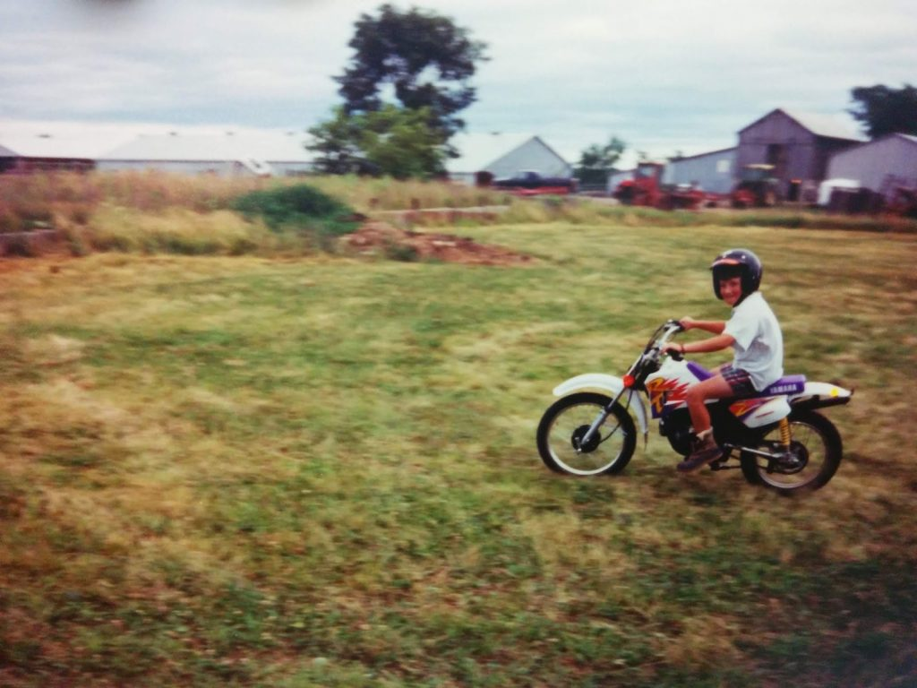 Thomas riding his motorcycle on the farm with the John Deere equipment in the background.