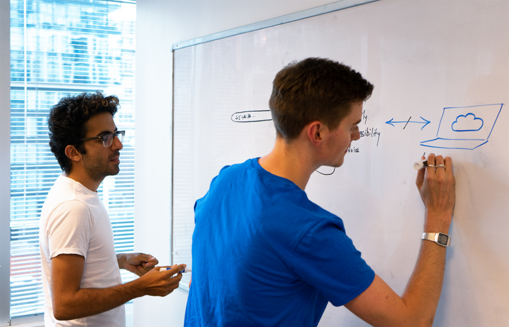 Two Connected employees writing on a whiteboard.