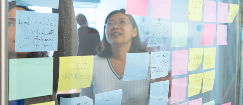 coworkers using sticky notes on wall to brainstorm and collaborate